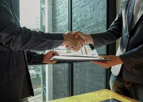 Businessman shakehand and exchanging contract documents. photo