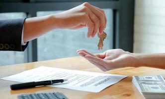The house broker sends the keys to the customer after signing the contract to buy the house. photo
