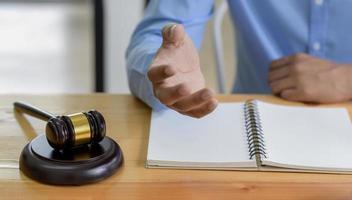 Primer plano de martillo sobre la mesa y abogado presentando la ley, el concepto de ley. foto