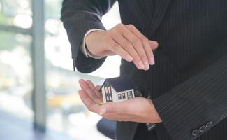 Insurance agent holds a house model in hand showing the symbol of home insurance. photo
