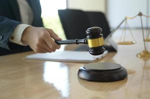 Concept of justice, Lawyer holding a hammer pretending to hit on a wooden tray put on the desk. photo