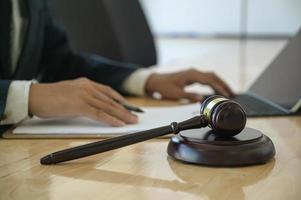 Concept of justice, Hammer placed on work desk with lawyer uses a laptop sitting behind. photo