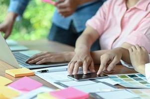un equipo de diseñadores de aplicaciones profesionales está diseñando pantallas móviles y usando computadoras portátiles. foto
