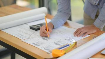 The architect is designing the construction. He drafts the floor plan to present to the client. photo