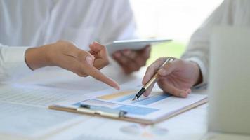 dos equipos de negocios discuten y analizan los gráficos del proyecto trabajando juntos en la oficina. foto