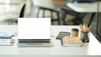 Blank screen laptop in modern workspace with office supplies. photo