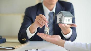 el corredor de venta de casa tiene las llaves y la casa modelo se entrega a los clientes, concepto de bienes raíces. foto