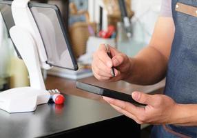 empleado sosteniendo un teléfono inteligente para guardar el menú del pedido del cliente. foto