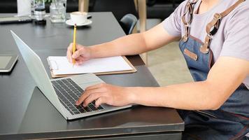 los empleados utilizan una computadora portátil y registran las ventas diarias. foto