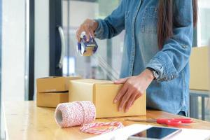 Teenage girls are packing products in boxes and using clear adhesive tape to deliver to customers. photo