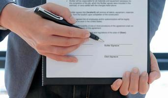 Cropped shot of The contractor pointed the pen at the builder to sign the contract to build the house. photo