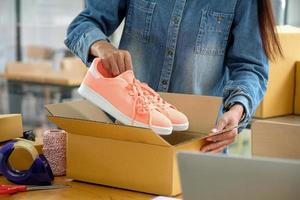 Online sellers are packing shoes in boxes to deliver to customers. photo