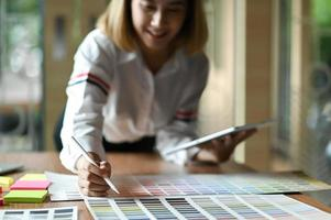 Asian female graphic designer working in office. She uses tablet and point the pen on color chart. photo