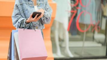 The shopper has a paper bag in his hand, searching for information on his smartphone. photo
