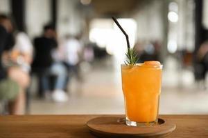 vaso de jugo de naranja en una bandeja de madera colocada sobre una mesa en el café fondo borroso. foto