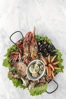 Plato gourmet de mariscos frescos mixtos en la mesa del restaurante español foto