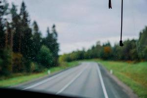 Rain water drop on the window. View of the road and the autumn forest photo