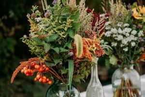ramos de estilo rústico en la mesa en jarrones y frascos de vidrio foto