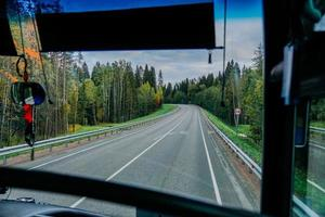 View of the road and the autumn forest through the bus window. Road trip photo