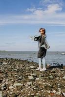 Young woman in sunglasses wrapped in a scarf, autumn on the Gulf of Finland photo