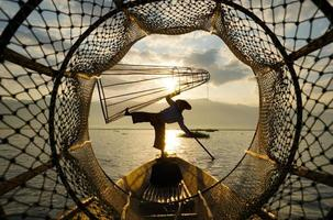 Ver a través del gallinero de los pescadores locales de pie en el barco en el lago al amanecer. foto