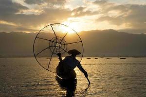 Silueta de pescador local usando coop para pescar en el lago Inle al amanecer. foto