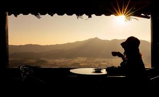 Young asian woman sitting in the hotel room near window, looking at the view of moutain and drink coffee in morning. tourism and vacation concept photo