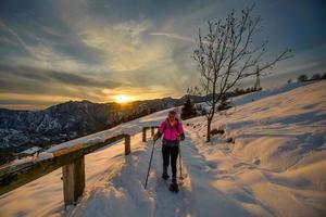 Mujer joven sola en caminata con raquetas de nieve en el hermoso día del atardecer foto