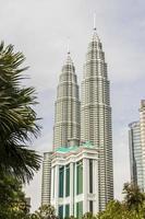 Petronas Twin Towers between palms in Kuala Lumpur, Malaysia. photo