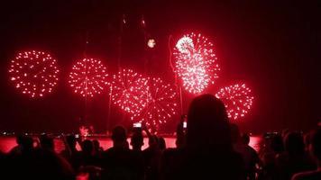 Spectators with smartphones watching fireworks video