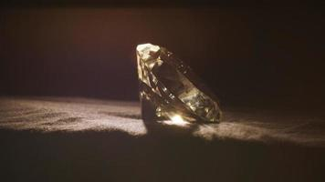 Large faceted diamond rotating on black background, wealth and luxury concept video
