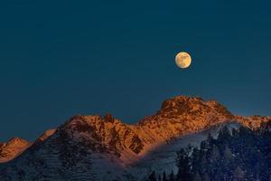 luna llena al atardecer en las montañas de invierno foto