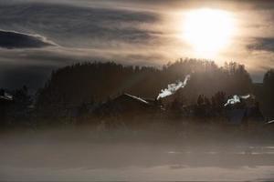 Humo de las chimeneas de un pueblo de montaña en el frío de la entrada al atardecer foto