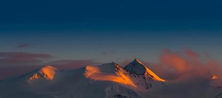 panorama de montañas nevadas puesta de sol roja foto