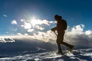 Man walking in the snow with snowshoes photo