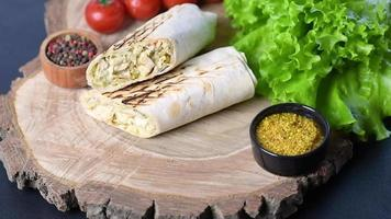 Delicious fresh shawarma with meat and vegetables on a dark concrete table video
