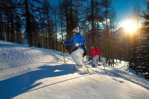 Excursion with snowshoes by two women at sunset, stock photo