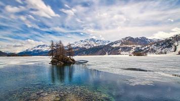 valle de la engadina. deshielo de primavera con islote en el lago foto