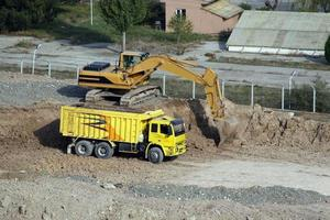 Trucks are waiting for the excavator to fill the soil. photo
