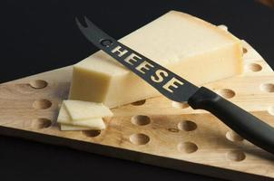 Cheese on a wood cutting table with a special knife for cheese and some slices photo