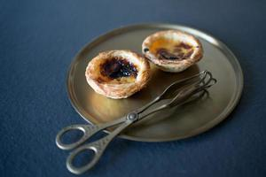 Close up of wo delicious Belem cakes, Pasteis de Belem on a bronze tray, with serving tongs. following portuguese traditional recipe. Portuguese Gastronomy. photo