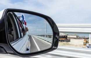 Car mirror with reflection of the road and the Russian flag photo