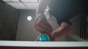 Low angle view shot on loft ceiling background, Man with face mask is cleaning hands and fingers with alcohol gel bottle to prevent bacterial infection, Coronavirus Covid-19, and healthy hygiene. video