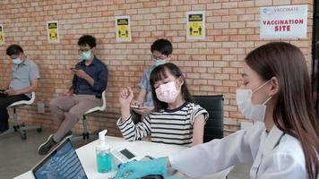 Asian female doctor injects a patient girl with people queuing at a social distance wearing face masks in the back to receive the preventing coronavirus COVID-19 vaccination in a hospital clinic. video