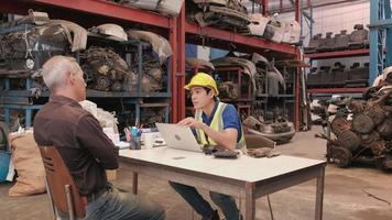 deux hommes dans un entrepôt de pièces détachées automobiles. client caucasien et vendeur de pièces de moteur asiatiques négociant un accord commercial en usine. video