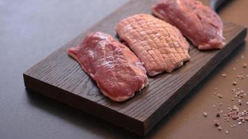 Raw duck breast with herbs and spices on a dark concrete background video