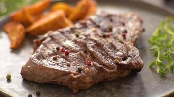Delicious juicy fresh beef steak with spices and herbs on a dark concrete background video