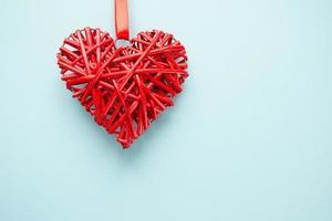 Ratán de mimbre corazón rojo sobre fondo azul. foto