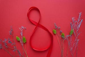 cinta roja satinada en forma de 8 sobre un fondo rojo foto