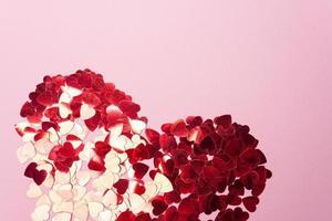 corazón de lentejuelas rojas sobre fondo rosa foto